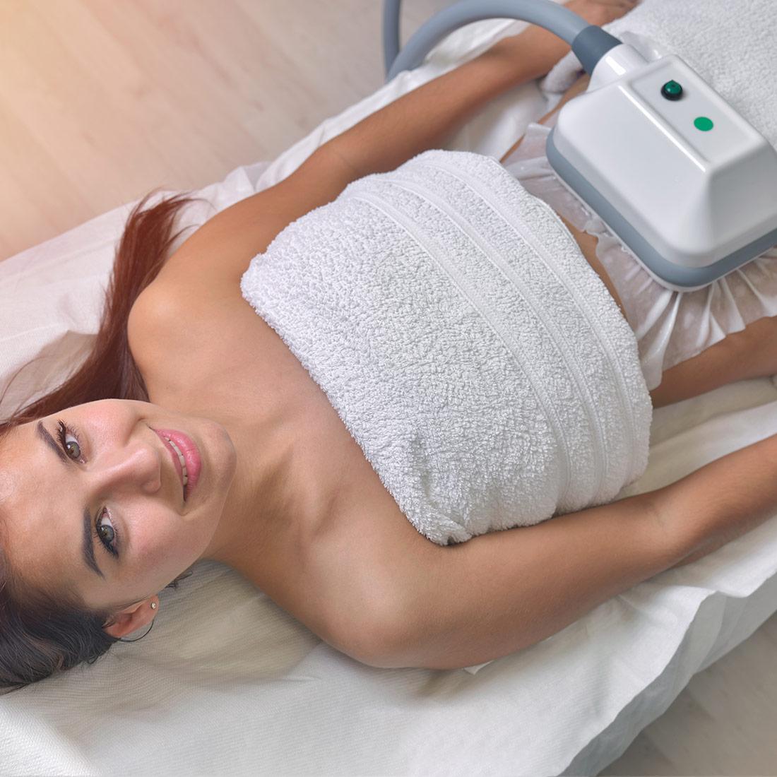 Όμορφη νεαρή γυναίκα σε κέντρο αισθητικής απολαμβάνει μια θεραπεία κρυολιπόλησης