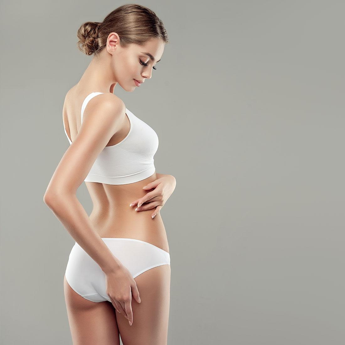 Φιγούρα λεπτού, νεανικού γυναικείου σώματος με λευκά ελαστικά εσώρουχα σε γκρί φόντο