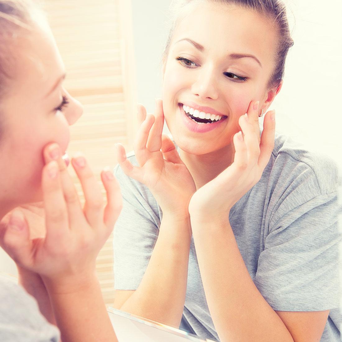 Έφηβη κοπέλα αγγίζει το πρόσωπό της μπροστά στον καθρέφτη, απολαμβάνοντας το καθαρό δέρμα της